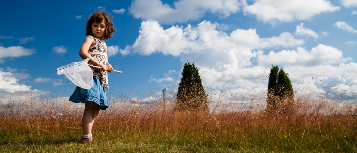 girl in a dress holding a butterfly net