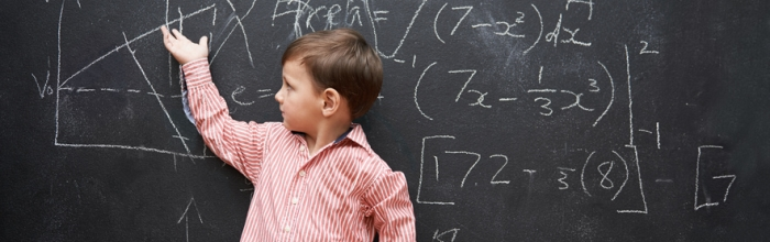 boy in a striped polo pointing at a blackboard